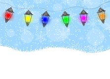 Garland with lanterns, blue sky and snow Royalty Free Stock Photos