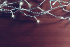 Garland LED light as Christmas holiday decoration. On wooden background royalty free stock photos