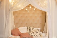 Garland of light bulbs hanging against a beige wall with curtains. beautiful bedroom with nice girl bed and many cute pillows. nob royalty free stock photos