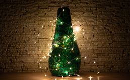 Garland lights around glass green vase on beige stone background royalty free stock photography