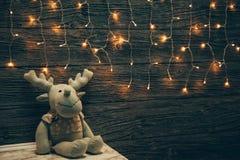 Garland Lights, cervo do brinquedo na placa de madeira do grunge velho Natal a Fotos de Stock Royalty Free