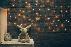 Garland Lights, ciervo del juguete, despertador en el tablero de madera del viejo grunge Imagenes de archivo