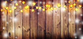 Garland with lights. Old wooden background. Celebratory lights. Stock Photo