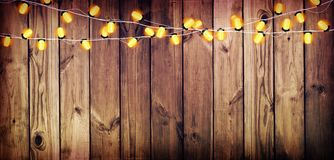 Garland with lights. Old wooden background. Celebratory lights. Stock Images