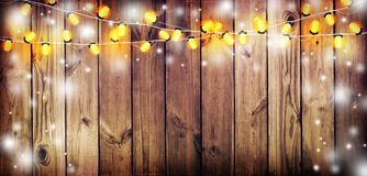Garland with lights. Old wooden background. Celebratory lights. Night party. Royalty Free Stock Images