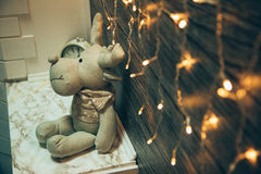Garland Lights, toy deer, alarm clock next to old grunge wooden Royalty Free Stock Images