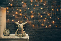 Garland Lights, toy deer, alarm clock on old grunge wooden board Stock Images