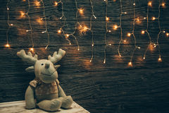 Garland Lights, toy deer on old grunge wooden board. Christmas a Royalty Free Stock Photos