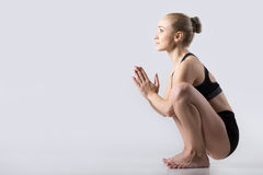 Garland, Malasana Pose. Sporty beautiful young woman practicing yoga, sitting in squat, Garland Pose, Malasana, stretching back muscles, hips, ankles, working Royalty Free Stock Photography