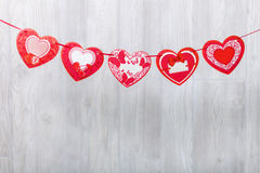 Garland of paper hearts. Greeting stretching. Wooden background royalty free stock images