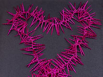 Garland of purple christmas beads forming a heart shape on  rustic light wood Stock Photo