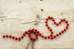 Garland of red christmas beads forming a heart shape on wood, lo Stock Photography