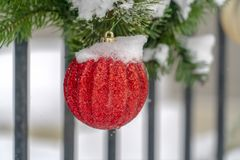 Garland with red glittered christmas ball ornament. Snowy garland with red glittered ball ornament decorating a porch railing. Close up view of beautiful royalty free stock images