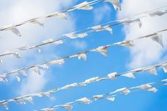 Garland of white flags of triangular shape, pennants in blue sky. City street holiday. Sea, marine theme. Modern. Garland of white flags of triangular shape Stock Photo