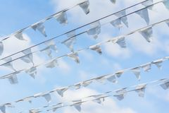 Garland of white flags of triangular shape, pennants in blue sky. City street holiday. Sea, marine theme. Modern. Diagonal garland of white flags of triangular Stock Photo