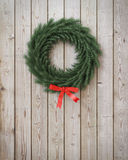Garland wreath with red ribbon on vintage wooden planks wall Stock Images
