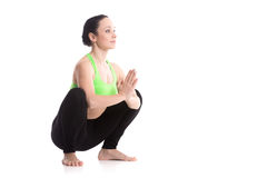 Garland yoga Pose. Smiling sporty girl on white background sitting in Garland yoga Pose, Malasana, yoga for stretching ankles, groins, back, strengthening belly Royalty Free Stock Photo