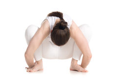 Garland yoga Pose. Sporty beautiful young woman in white sportswear sitting in squat, Garland Pose, Malasana, stretching back muscles, hips, ankles, studio full Stock Photo
