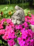 Garlanded Gnome. A happy garden gnome is surrounded by flowers stock photos