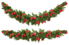 Garlands with Bows. Christmas garlands decorated with red velvet bows, isolated on white.  One garland is straight, and the other curved Royalty Free Stock Photos
