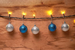 Garlands and Christmas balls on wooden wall Stock Photos