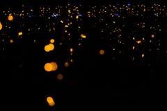 Garlands glow orange and yellow lights on the window