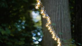 Garlands of Lamps. On a stand on the street. Light outdoor Bokeh Light bulb decor in outdoor party. Decorative outdoor string lights hanging on tree in the stock video footage