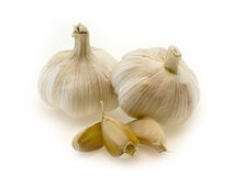 Garlic. Two bulbs and three cloves of garlic on a white background royalty free stock image