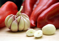 Garlic. Clove of garlic in the kitchen with red pepper in the background royalty free stock image