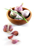 Garlic. And green onions in a wooden bowl. Isolated on a white background royalty free stock photo