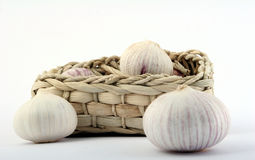 Garlic. Some garlic heads and a basket container on plain background Royalty Free Stock Photo