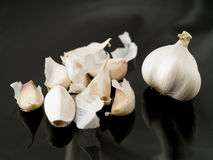 Garlic. A closeup view of a garlic bulb and garlic cloves isolated on a black background Royalty Free Stock Images