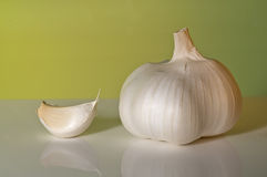 Garlic. Studio shot of a garlic and a clove on a green surface Stock Image