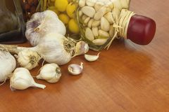 Garlic, aromatic ingredients for flavoring food. Home remedy for colds and flu. Garlic marinated in olive oil. Stock Photos