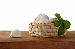 Garlic and basil in a basket on a cutting board. Stock Photos