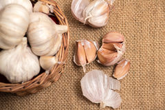 Garlic on basket. Some garlic heads on a basket container on burlap background Stock Photography