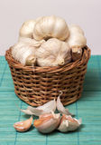 Garlic on basket. Some garlic heads and a basket container on plain background Royalty Free Stock Image