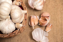 Garlic on basket. Some garlic heads and a basket container on plain background Stock Photos