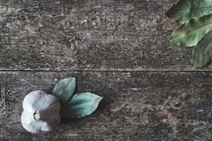 Garlic and bay leaf. Dry bay leaf and garlic on the wooden rustic background, top view. Bay leaf and garlic background Royalty Free Stock Photography