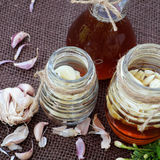 Garlic in bee honey, remedy skin care. Healthy food from nature herbal, garlic soak in bee honey, a herb remedy for skin care, healthcare, three jar on green Royalty Free Stock Photos