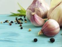 garlic, black pepper bottle oil aromatic freshness kitchen nutrition vegetable on blue wood Stock Images