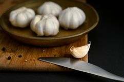 Garlic and black pepper on a wooden dashboard royalty free stock photography