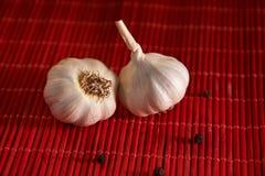 Garlic, black pepper on a red wooden table. Food background. Garlics. sliced garlic, garlic clove, garlic bulb. Garlic, black pepper on a wooden table. Garlics stock images