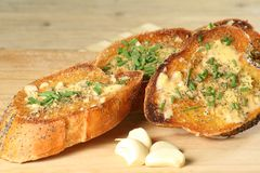 Garlic bread. Slices of toasted garlic bread with chopped chives on a wooden board Royalty Free Stock Images