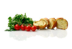 Garlic Bread. Studio macro of sliced crusty garlic and cheese Italian bread, parsley herbs and cherry tomatoes on a white background with soft shadows. Copy royalty free stock image