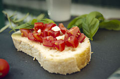 Garlic bread bruschetta with cherry tomatoes and ingredients. On a black stone dish Stock Photography