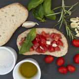 Garlic bread bruschetta with cherry tomatoes and ingredients. On a black stone dish Stock Photo