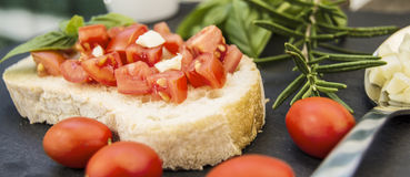 Garlic bread bruschetta with cherry tomatoes and ingredients. On a black stone dish Royalty Free Stock Photography