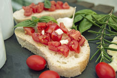Garlic bread bruschetta with cherry tomatoes and ingredients. On a black stone dish Stock Images