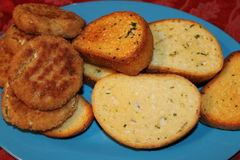 Garlic Bread and Crab patties. On a blue plate Royalty Free Stock Images